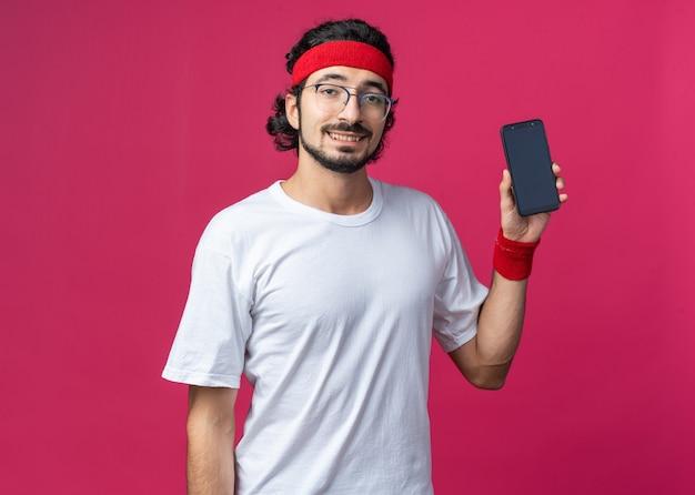 Glimlachende jonge sportieve man met hoofdband met polsbandje met telefoon