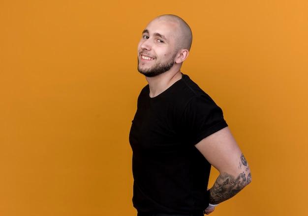 Glimlachende jonge sportieve man met polsbandje hand in hand achter rug geïsoleerd op oranje muur met kopie ruimte