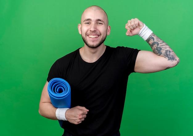 Glimlachende jonge sportieve mens die de yogamat van de polsband draagt en sterk gebaar toont dat op groene muur wordt geïsoleerd