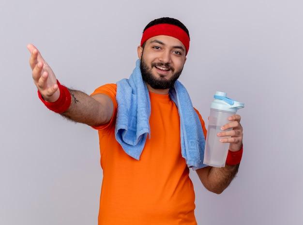 Glimlachende jonge sportieve mens die hoofdband en polsband draagt die waterfles met handdoek op schouder houdt die hand bij camera uithoudt die op witte achtergrond wordt geïsoleerd