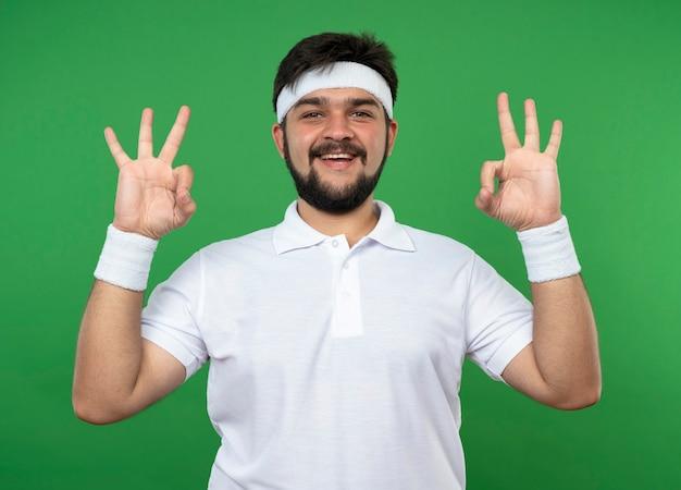 Glimlachende jonge sportieve mens die hoofdband en polsbandje draagt die meditatiegebaar tonen dat op groen wordt geïsoleerd