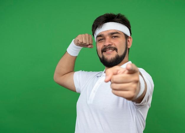 Glimlachende jonge sportieve mens die hoofdband en polsbandje draagt die sterke gebaarpunten toont die op groene muur met exemplaarruimte worden geïsoleerd