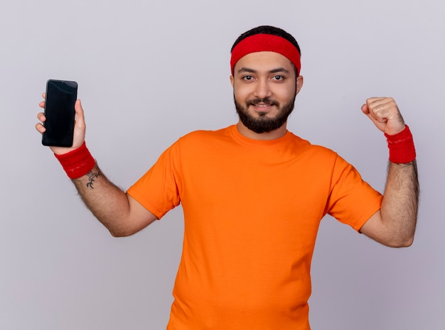 Glimlachende jonge sportieve mens die hoofdband en polsbandje draagt die telefoon houdt en sterk gebaar toont dat op witte achtergrond wordt geïsoleerd