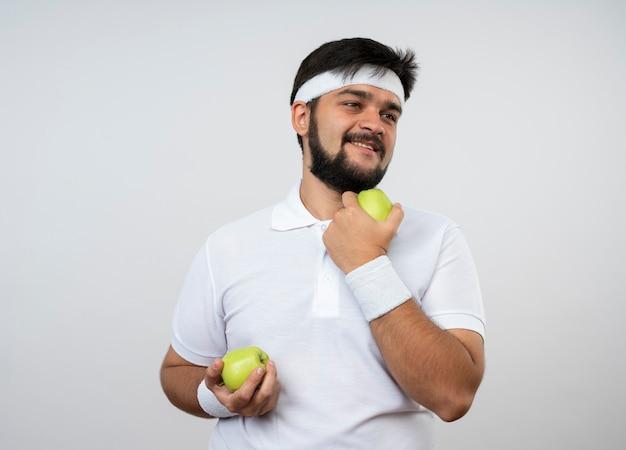 Glimlachende jonge sportieve mens die kant bekijkt die hoofdband en polsbandje draagt ?? die appels houdt die op witte muur worden geïsoleerd