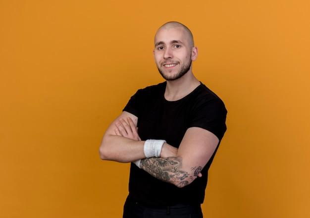 Glimlachende jonge sportieve mens die polsbandje draagt die handen kruisen die op oranje muur worden geïsoleerd