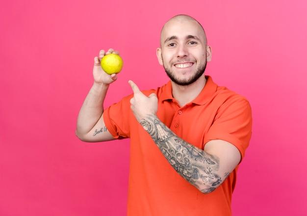 Glimlachende jonge sportieve mensenholding en wijst naar appel die op roze muur wordt geïsoleerd