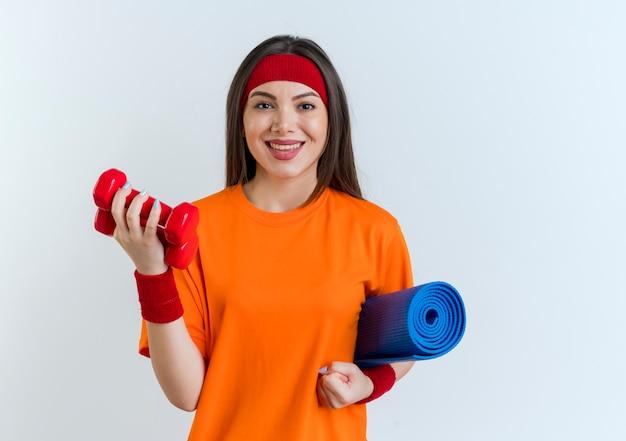 Glimlachende jonge sportieve vrouw die hoofdband en polsbandjes draagt die yogamat en domoren houden die op witte muur met exemplaarruimte wordt geïsoleerd