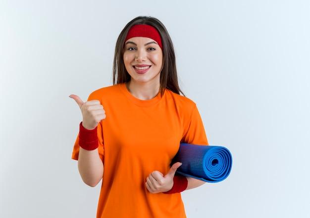 Glimlachende jonge sportieve vrouw die hoofdband en polsbandjes draagt die yogamat houden die duimen tonen die omhoog op witte muur met exemplaarruimte worden geïsoleerd