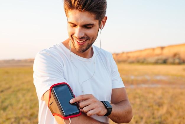 Glimlachende jonge sportman die de mobiele telefoon van het lege scherm op armband in openlucht gebruikt