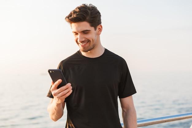 Glimlachende jonge sportman in zwarte t-shirt