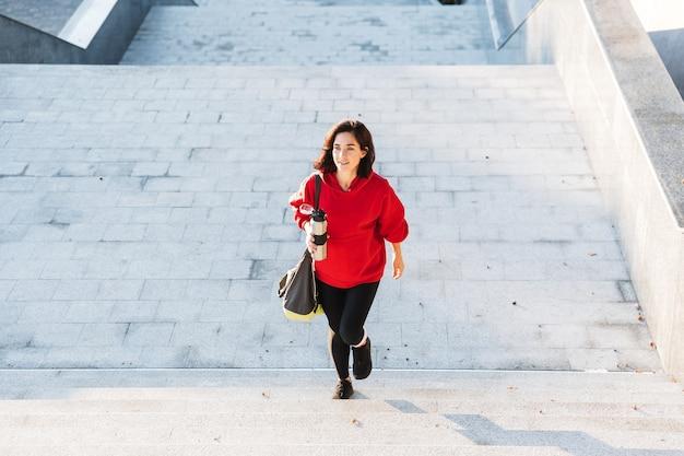 Glimlachende jonge sportvrouw die een hoodie draagt die buiten loopt, die sporttas draagt, die koffiekop houdt
