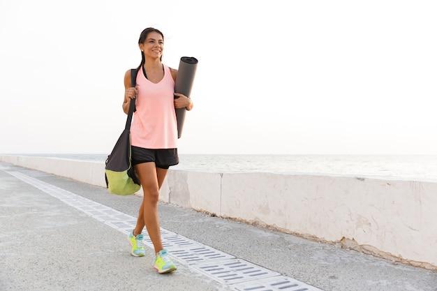 Glimlachende jonge sportvrouw fitness mat te houden