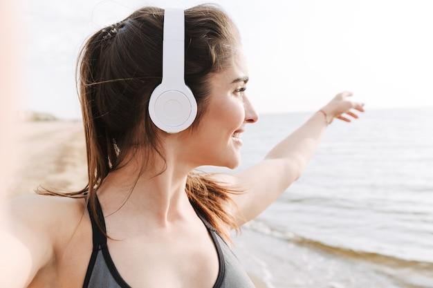 Glimlachende jonge sportvrouw met hoofdtelefoons