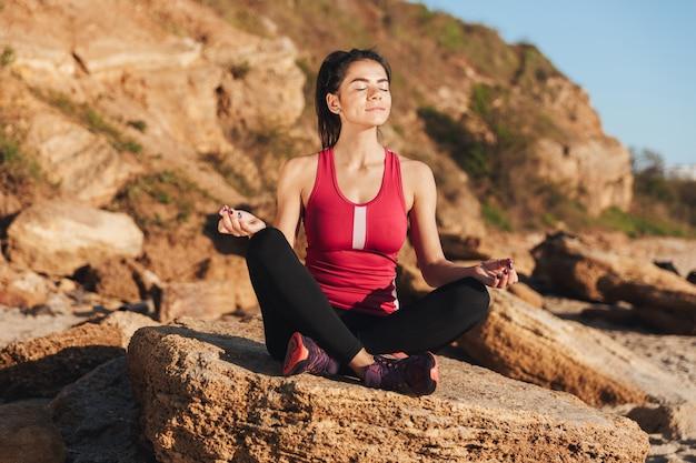Glimlachende jonge sportvrouwenzitting in yogapositie