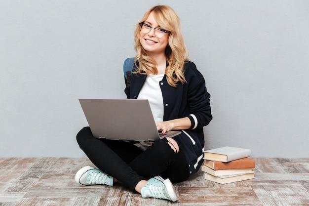 Glimlachende jonge studente die laptop computer met behulp van.