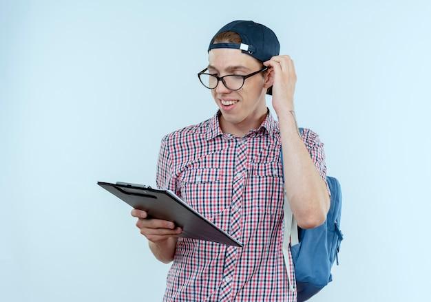 Glimlachende jonge studentenjongen met een achtertas en een bril en een pet die vasthoudt en naar het klembord kijkt en de hand op het hoofd zet
