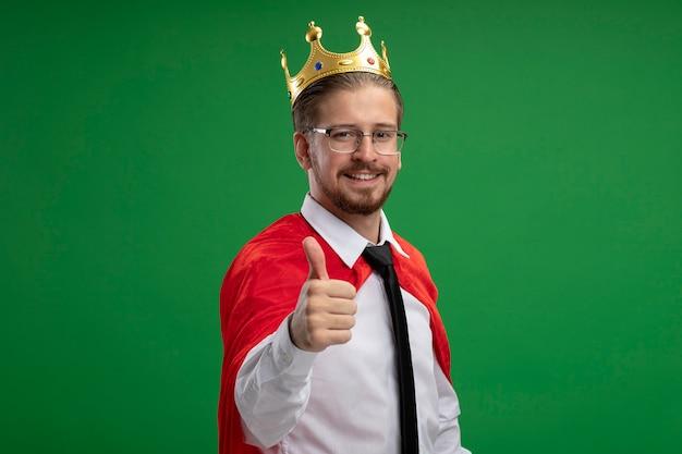 Glimlachende jonge superherokerel die kroon draagt die duim toont die omhoog op groene achtergrond wordt geïsoleerd