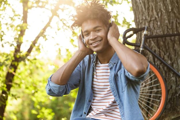 Glimlachende jonge tiener met fiets in openlucht