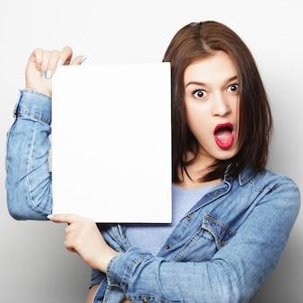 Glimlachende jonge toevallige stijlvrouw die leeg uithangbord, over witte geïsoleerde ruimte toont