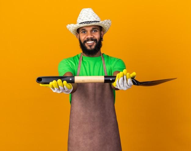 Glimlachende jonge tuinman afro-amerikaanse man met een tuinhoed en handschoenen die een schop aan de voorkant vasthouden, geïsoleerd op een oranje muur
