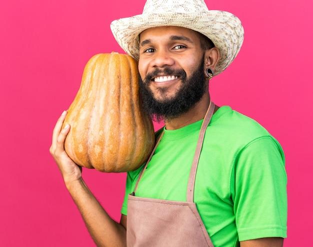 Glimlachende jonge tuinman afro-amerikaanse man met een tuinhoed met pompoen