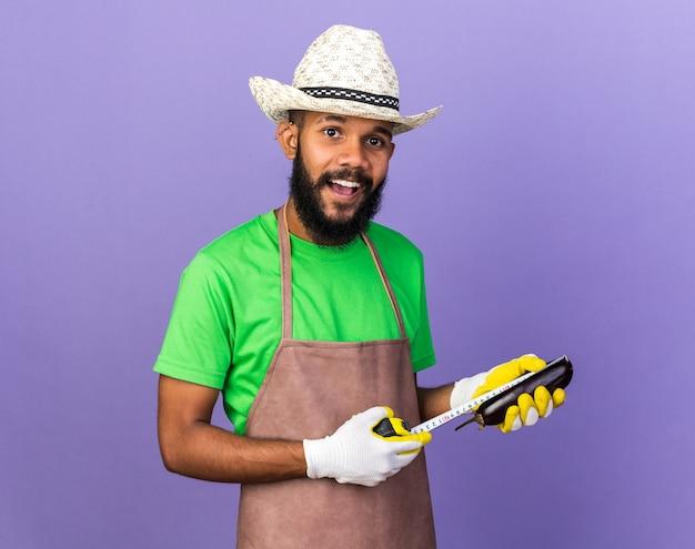Glimlachende jonge tuinman afro-amerikaanse man met tuinhoed en handschoenen die aubergine meten met meetlint geïsoleerd op blauwe muur