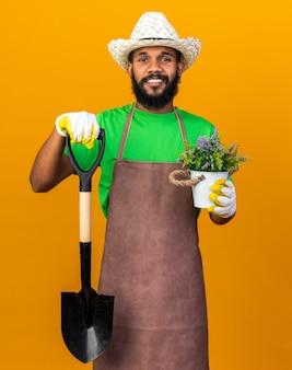 Glimlachende jonge tuinman afro-amerikaanse man met tuinhoed en handschoenen met schop met bloem in bloempot geïsoleerd op oranje muur