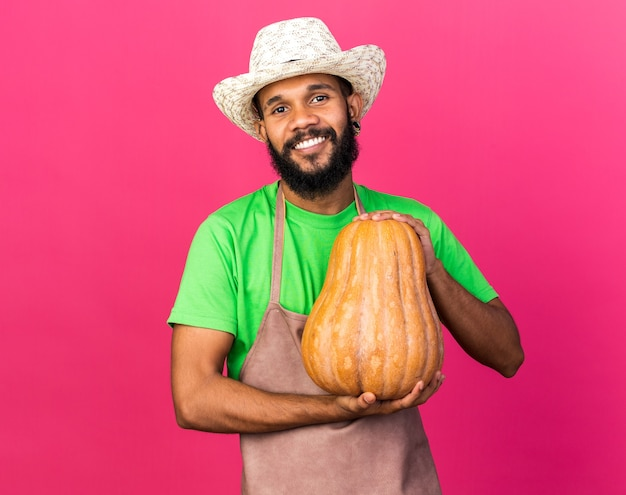 Glimlachende jonge tuinman afro-amerikaanse man met tuinhoed met pompoen geïsoleerd op roze muur