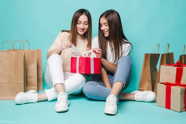 Glimlachende jonge twee meisjes die vloerboodschappentassen zitten en giften op de turkooise muur openen.