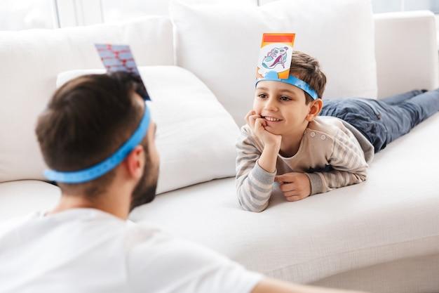 Glimlachende jonge vader die plezier heeft met zijn gelukkige zoon en thuis naar elkaar kijkt