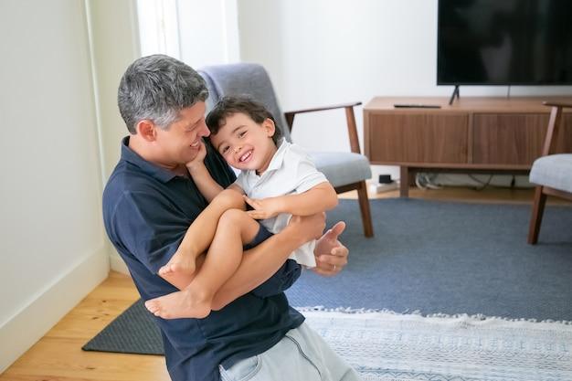 Glimlachende jonge vader die zijn zoon in handen houdt en op knieën in de woonkamer staat.