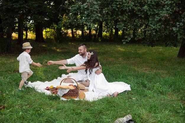 Glimlachende jonge vader en moeder die op plaid in het park rusten terwijl hun kleine kind in hun armen loopt. familie- en vrijetijdsconcept