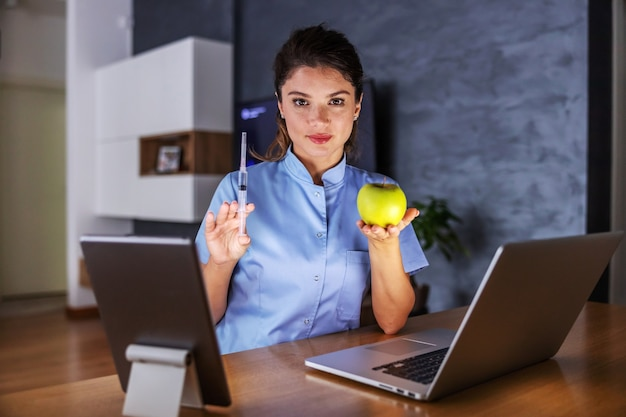 Glimlachende jonge verpleegster om thuis te zitten en appel in één hand te houden en spuit met een remedie in andere.