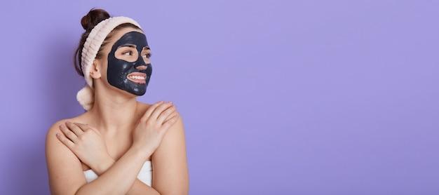Glimlachende jonge volwassen vrouw in haarband met zwart gezichtsmasker die kosmetische procedures doen