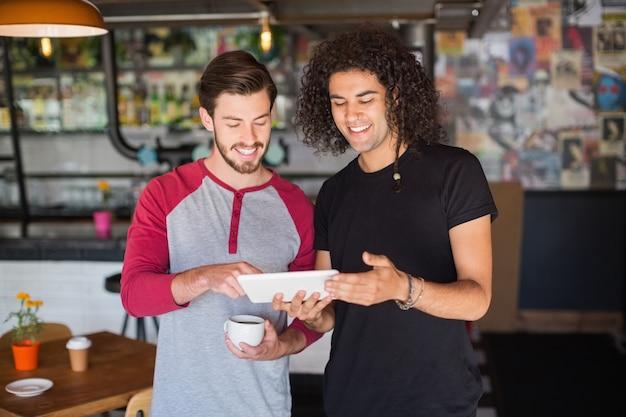 Glimlachende jonge vriend die digitale tablet in restaurant met behulp van