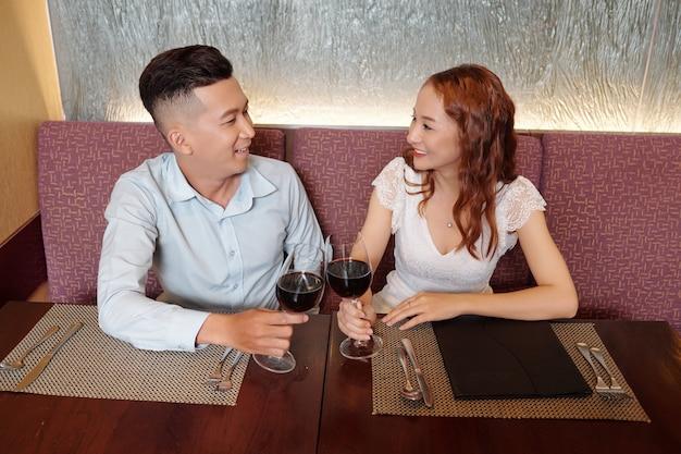 Glimlachende jonge vriend en vriendin kijken elkaar aan als ze met glazen wijn hun eerste verjaardag vieren