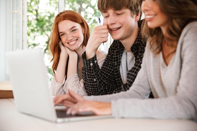 Glimlachende jonge vriendenstudenten die laptop computer met behulp van.