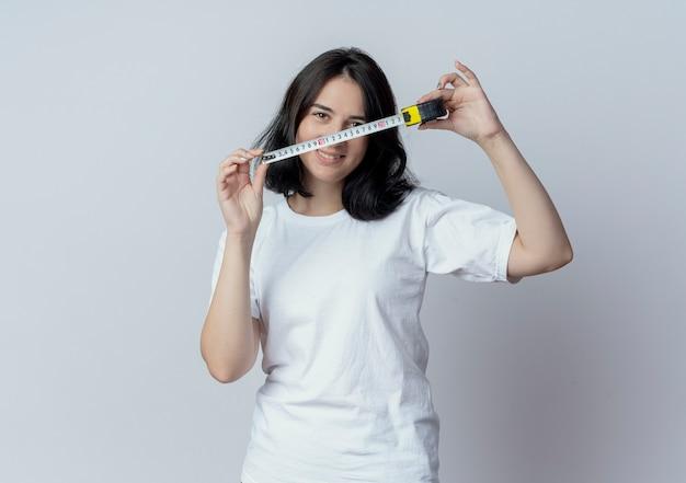 Glimlachende jonge vrij kaukasische de bandmeter van de meisjesholding die op witte achtergrond met exemplaarruimte wordt geïsoleerd