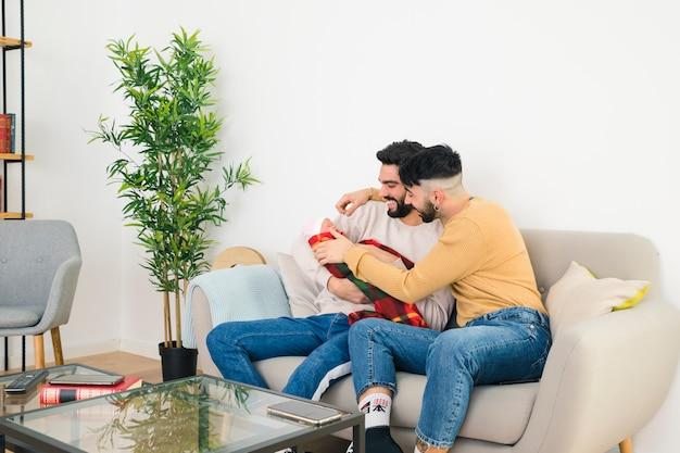 Glimlachende jonge vrolijke paarzitting op bank die van hun baby houden