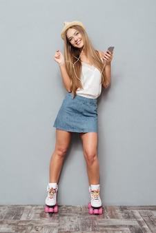 Glimlachende jonge vrolijke rolvrouw in hoed het luisteren muziek met smartphone die op een grijze achtergrond wordt geïsoleerd