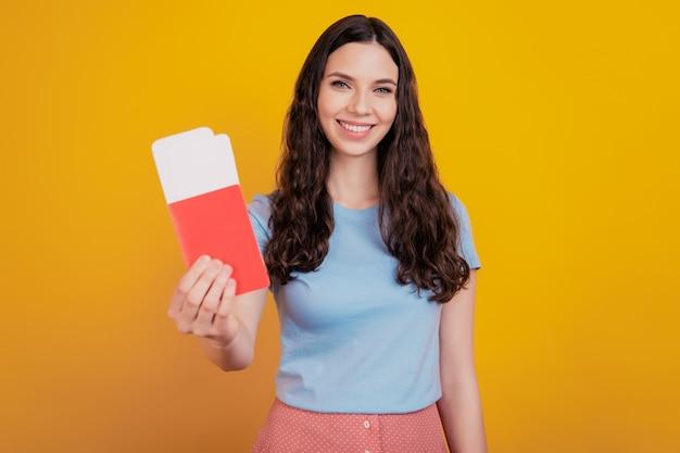 Glimlachende jonge vrolijke vrouw houdt paspoort tickets instapkaart reizen naar het buitenland geïsoleerd op felgele kleur muur achtergrond