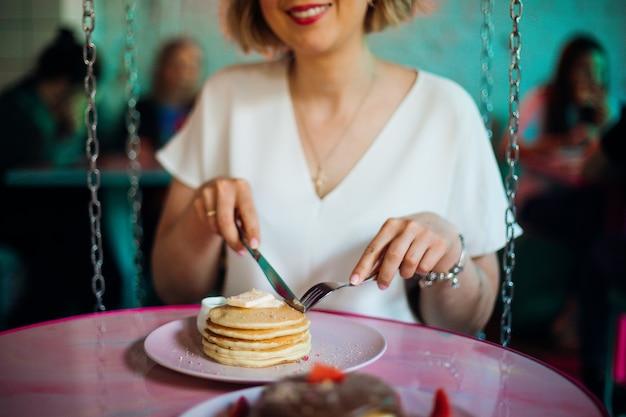 Glimlachende jonge vrouw begint zoete pannenkoeken met honing te proeven. concept van goede voeding.