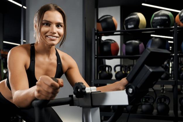 Glimlachende jonge vrouw bezig met hometrainer
