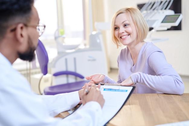 Glimlachende jonge vrouw bezoekende arts