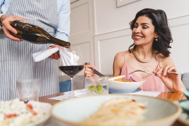 Glimlachende jonge vrouw die aan tafel zit met heerlijk eten terwijl cafémedewerker alcoholische drank in glas giet