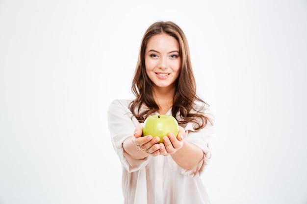 Glimlachende jonge vrouw die appel geeft aan voorzijde geïsoleerd op een witte muur
