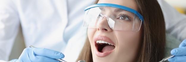 Glimlachende jonge vrouw die behandeling ondergaat bij tandheelkundige kliniekclose-up