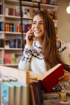 Glimlachende jonge vrouw die boek vasthoudt terwijl ze aan het telefoneren is in de bibliotheek