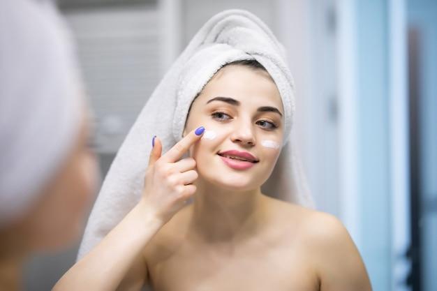 Glimlachende jonge vrouw die crème op het gezicht aanbrengt en thuis de badkamer wil spiegelen