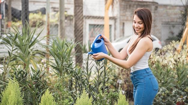 Glimlachende jonge vrouw die de installatie in de serre water geeft